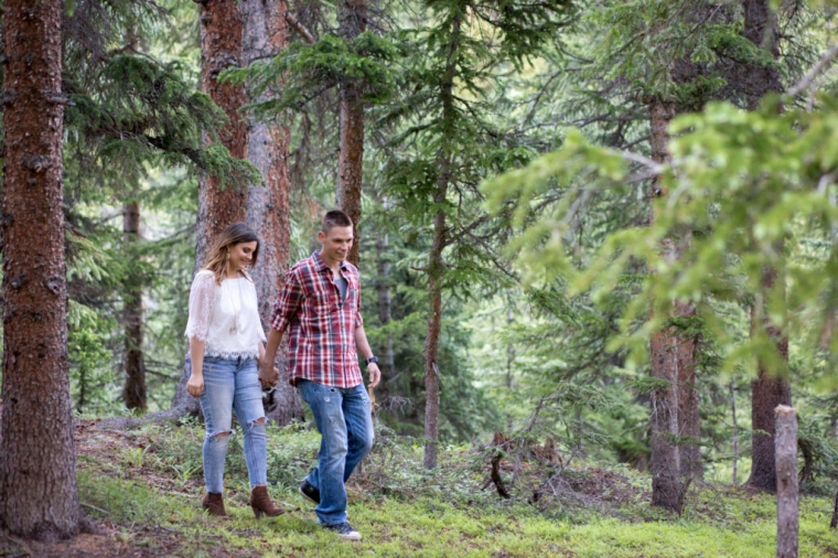 loveland pass engagement session colorado couple holds hands and walks in forest